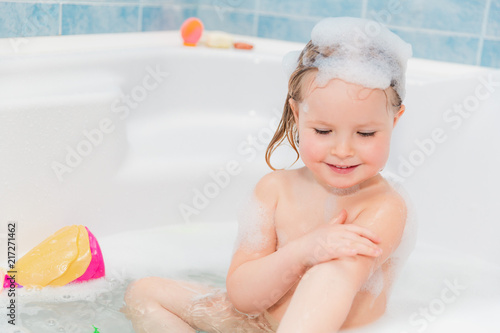 little girl washing herself at bath with soap on head #217271462