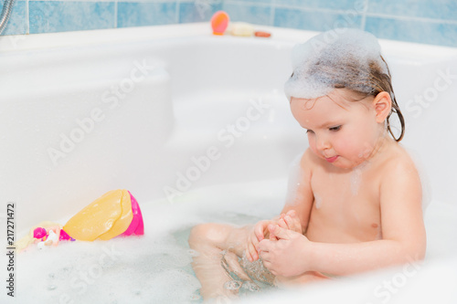 little girl washing herself at bath with soap on head #217271472