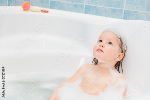 little girl have fun in the bath with soap on head #217271499