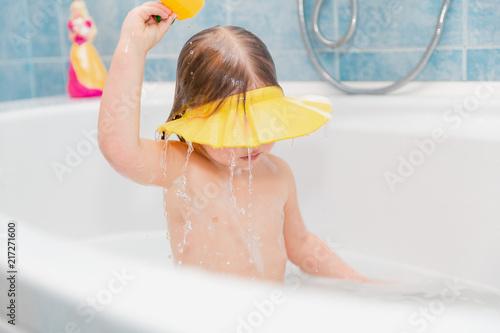 little girl washing her head herself wearing visor from water #217271600