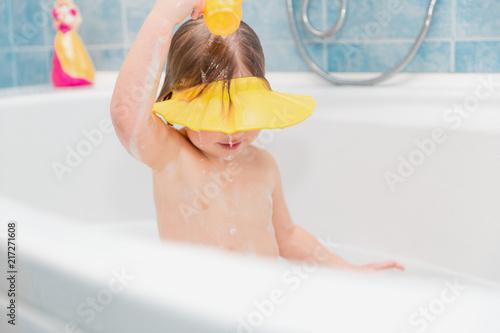 little girl washing her head herself wearing visor from water #217271608