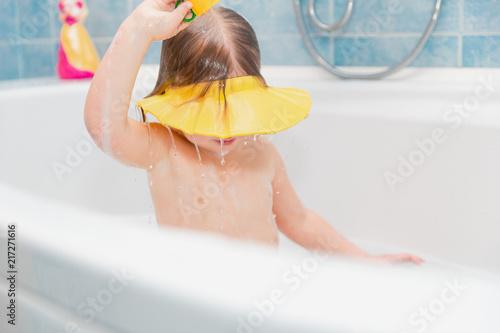 little girl washing her head herself wearing visor from water #217271616