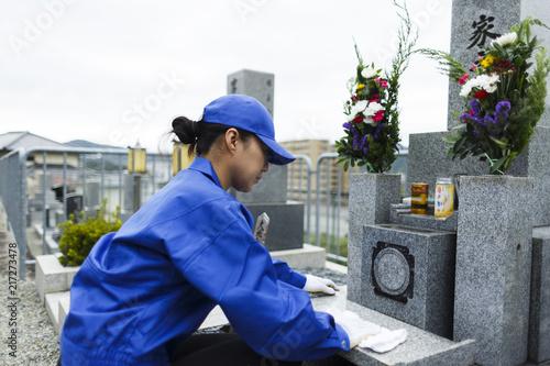 お墓の掃除をする作業服の女性 Canvas Print