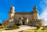 Facade of a medieval castle palace under a blue sky (Manzanares el Real, Spain)