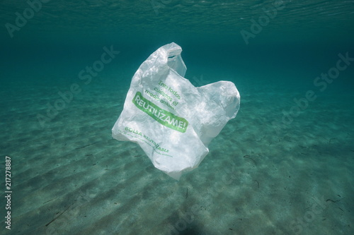 Wallpaper Mural Plastic pollution underwater, a bag with text in Spanish together we take care