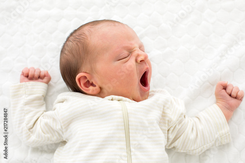 From above of newborn baby in white overall sleeping and yawning adorably lying on white blanket