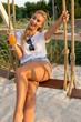 Portrait einer jungen Frau im Freien, die auf einer Schaukel sitzt, einen Drink geniesst, lächelt und fröhlich ist
