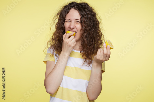 Fotografie, Tablou  Portrait of cute Caucasian female with disgusting expression tastes sour lemon, frowns in displeasure, isolated over yellow studio wall background