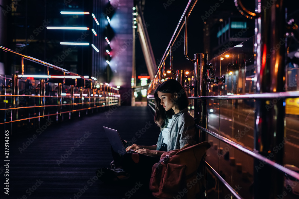Fototapeta side view of young woman using laptop on street with night city lights on background