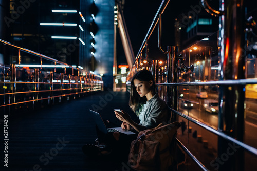 side view of young woman with laptop on knees using smartphone with night city on background - 217314298