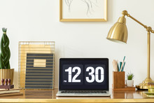 Laptop Showing The Time, Notebooks, Plant And Lamp On A Desk In An Office Interior. Real Photo