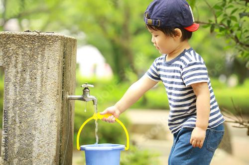 Fotografie, Tablou  バケツに水を汲む男の子