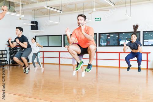 Fotografie, Obraz  Clients Doing Tuck Jumps On Hardwood Floor In Gym