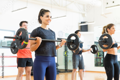 Fotografie, Obraz  Woman Smiling While Lifting Barbell In Health Club
