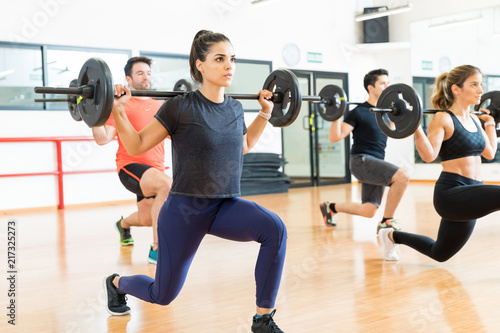 Fototapeta  Weightlifter Lifting Barbell While Doing Lunges With Friends