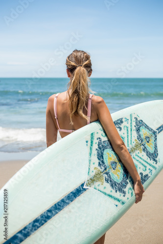 Beautiful young slim girl in sexy pink bikini with long custom surfing board single fin in front of blue ocean ready to surfing Wallpaper Mural