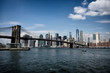 Brooklyn bridge with New York City skyline panoramic spring view. Lower Manhattan downtown scenery from Brooklyn Bridge Park riverbank in Dumbo district, NYC, USA.