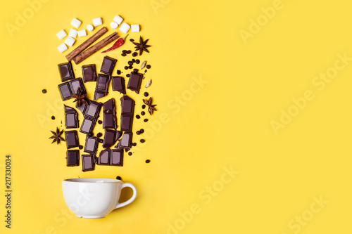 Foto auf Leinwand Schokolade Hot chocolate cup, chocolate pieces, spices and marshmallows on yellow background
