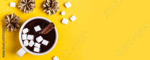 Hot chocolate cup with cinnamon and marshmallow on yellow background. Warming Christmas winter drink