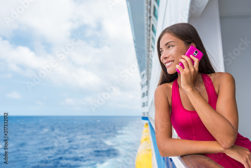 Cruise ship woman using mobile cellphone calling on travel vacation. Asian girl on travel holidays. Internet international call concept. Tourist talking on smartphone at sea.