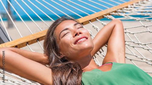 Sun tan sleeping woman on beach hammock on Caribbean tropical vacation getaway. Zen wellness Asian girl relaxing smiling happy at outdoor hotel.