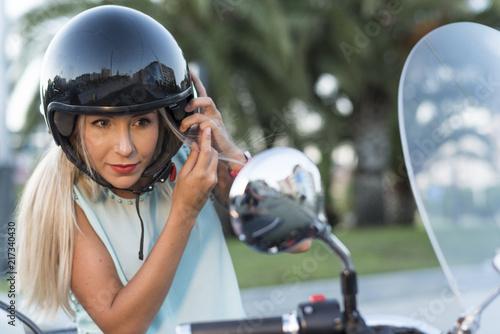 Attractive blonde woman with helmet n custom sidecar bike looking at