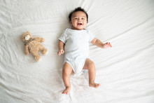 Adorable Baby Boy In White Sunny Bedroom In Winter Morning. Newborn Child Relaxing In Bed. Family Morning At Home. Newborn Kid During Tummy Time Smiling Happily At Home