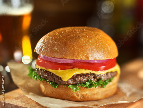 tasty cheeseburger with beer in background