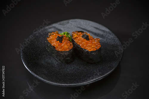 Foto op Canvas Klaar gerecht Ikura Nigiri, Salmon Eggs, Sushi bar menu, Sushi, traditional Japanese food on ceramic dish, Japanese food style, Japanese menu, Fresh Salmon eggs sushi on black background, selective focus