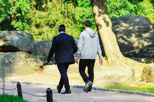 2 man, the Hasidim Jews are walking in the park in Uman, Ukraine, the time of the Jewish New Year, Rosh Hashanah