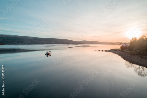 Photo Small Fishing Boat in Calm Lake at Sunset