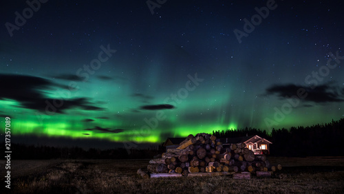 Valokuva  Northern Lights with a isolated house in the foreground