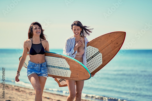 Women surfers walking on the beach and having fun in summer Vacation. Extreme Sport.