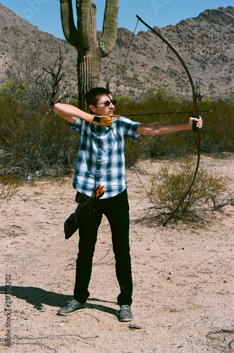Fotografie, Obraz  The Traditional Archer with a long bow in the desert