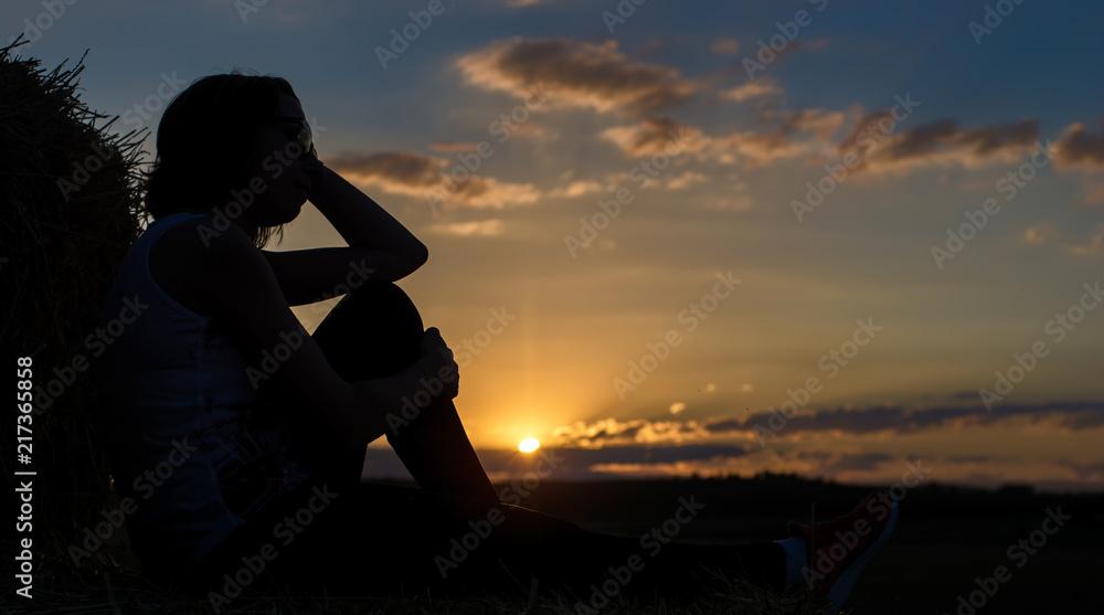 Fototapeta Frau genießt in freier Natur den malerischen Sonnenuntergang
