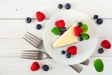 Slice Of Cheesecake With Blueberries And Raspberries, Top View Scene Over A Bright, White Wood Background