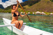 Happy woman Kayaking in the Ocean on Vacation at a tropicls