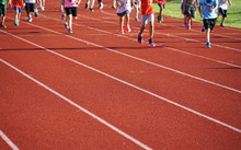 Kids Running On Red Outdoor Track In Sport Field