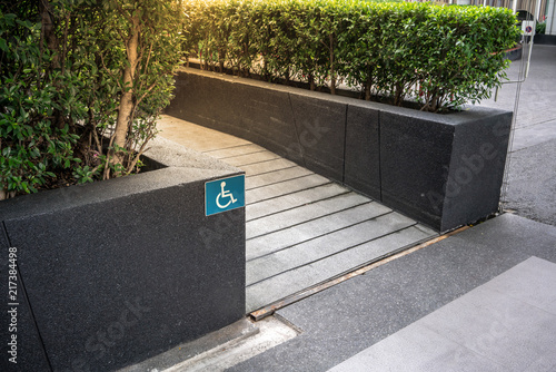 Foto  Ramped access, using wheelchair ramp with information sign on floor background