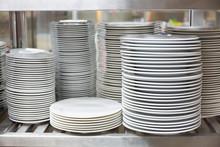 White Ceramic Dinnerware On Restaurant Stainless Shelves.