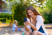 Young Mother Laughing At A Text Message
