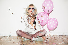 Pretty Girl In Sunglasses With Pink Balloons Happily Sending Air Kiss On Camera With Confetti Around Over White Background Isolated