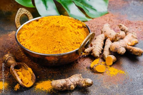 Cadres-photo bureau Condiment Turmeric powder and fresh root on grunge background