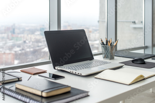 Valokuva  Workplace with notebook laptop Comfortable work table in office windows and city view