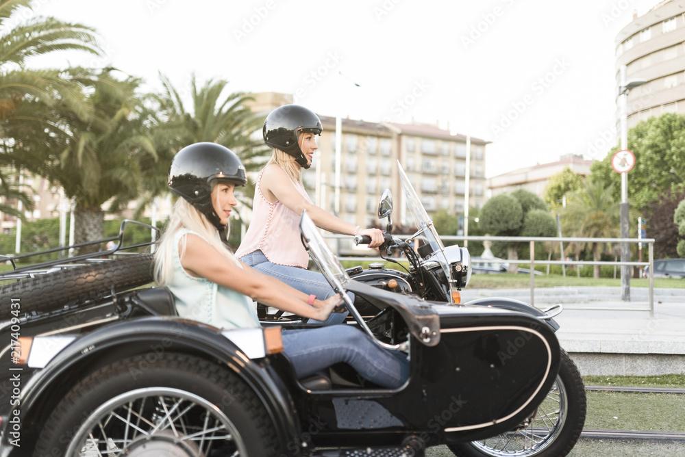 Fototapeta Two happy sister blonde women on sidecar bike smiling and happy