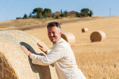 Valokuva  Farmer working on field near bale of wheat