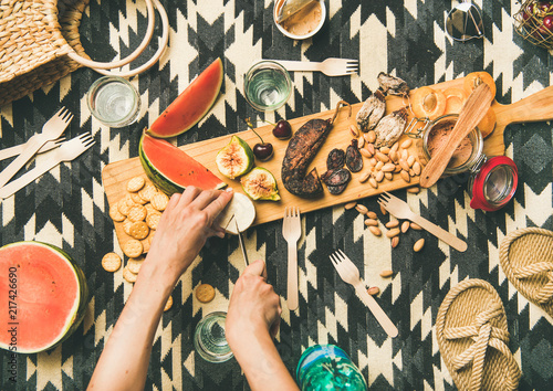 Keuken foto achterwand Summer picnic setting. Flat-lay of fresh fruit, smoked sausage, nuts, pate, cracker, straw accessories and woman hands cutting brie cheese over linen blanket, top view. Outdoor gathering or lunch