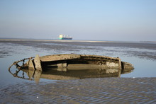 A Sunken Boat At A Mudflat Wit...
