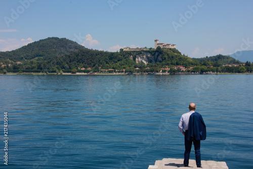 Fotografering  Uomo guarda la Rocca di Angera ad Arona, Lago Maggiore, Piemonte, Italia