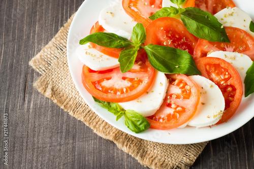 Láminas  Close-up photo of caprese salad with ripe tomatoes, basil, buffalo mozzarella cheese